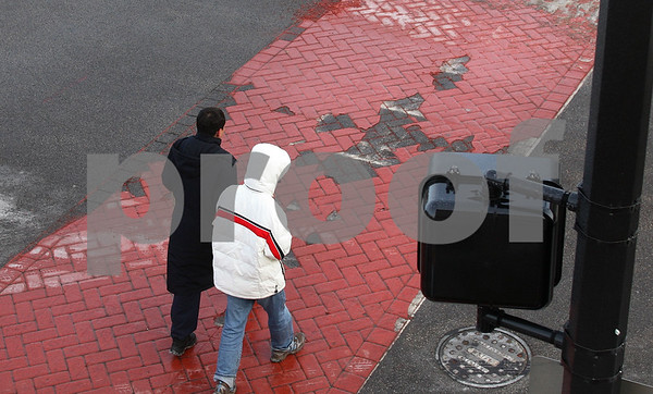 Kyle Bursaw – kbursaw@daily-chronicle.com<br /> <br /> Two people cross 2nd street where it intersects with Lincoln Highway. The crosswalk, which was stamped and put in earlier this year, is already showing visual damage. <br /> <br /> 12/15/10