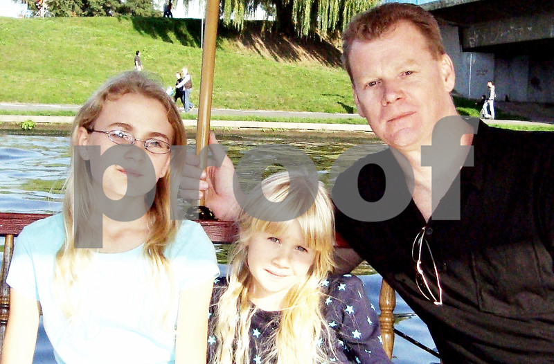 During a visit to Krakow, Poland in September 2009, Sean McKnight (right) and his children Kelly (right), now 14, and Julia, now 7, take a tour boat ride on the Vistula River.