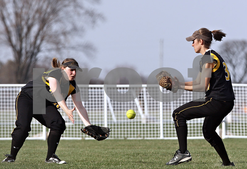 Beck Diefenbach  -  bdiefenbach@daily-chronicle.com<br /> <br /> Neither Sycamore's Nicole Schroeder (16, left) nor Anna Buzzard (30, right) are able to catch a pop fly during the top of the second inning of the game against Genoa-Kingston at Sycamore High School in Sycamore, Ill., on Thursday April 1, 2010. G-K defeated Sycamore 9 to 2.