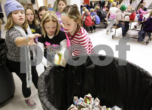 Kyle Bursaw – kbursaw@daily-chronicle.com<br /> <br /> Sydney Clark, left, tosses her empty milk into the recycling bin as fellow third-graders Isabella Nordstrum, center, and Lucia O'Brien, right, drain their unfinished milk into a bucket during lunch time at West Elementary school in Sycamore, Ill. on Nov. 18, 2010.