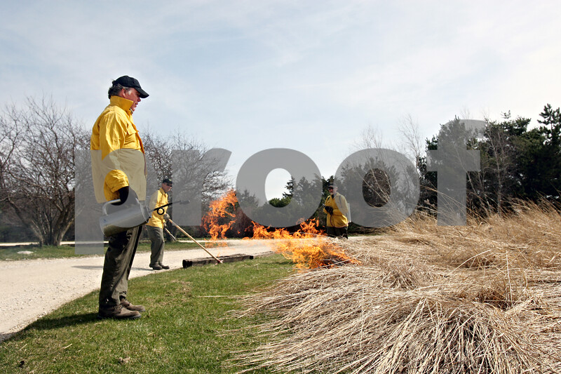 Rob Winner – rwinner@daily-chronicle.com<br /> <br /> Terry Hannan (left), DeKalb County Forest Preserve Superintendent, starts a controlled prairie burn at Afton Forest Preserve in DeKalb, Ill. on Wednesday March 31, 2010.
