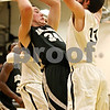 Rob Winner – rwinner@daily-chronicle.com<br /> Kaneland's Tyler Callaghan (left) looks to pass under the Kaneland basket, while Luke Johnson provides pressure for Sycamore in the first quarter.