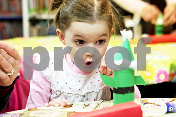 Rob Winner – rwinner@daily-chronicle.com<br /> <br /> DeKalb resident Lilly Underwood, 3, and her mother, Shawna, use a cardboard tube, construction paper, glue and cotton balls to create an elf and Santa Claus at the DeKalb Public Library on Monday afternoon.