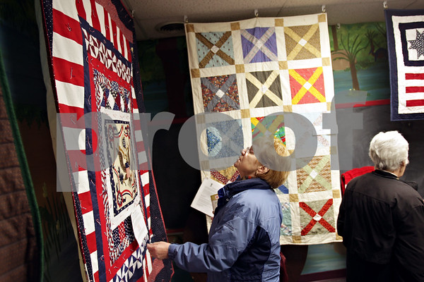 Beck Diefenbach  -  bdiefenbach@daily-chronicle.com<br /> <br /> Pat Ridey, of Genoa, examines a quilt of valor on display at the Genoa Public Library in Genoa, Ill., on Monday Jan. 25, 2010. The quilt was made for 1st. Lt. Brian D. Slavenas, who was killed in Fallujah, Afghanistan.