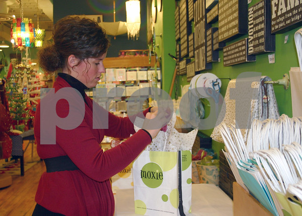 Moxie employee Abbie Simmons wraps up gift bags during Small Business Saturday, a state initiative sponsored by American Express OPEN to encourage shoppers to support local small businesses.<br /> <br /> By Nicole Weskerna nweskerna@daily-chronicle.com