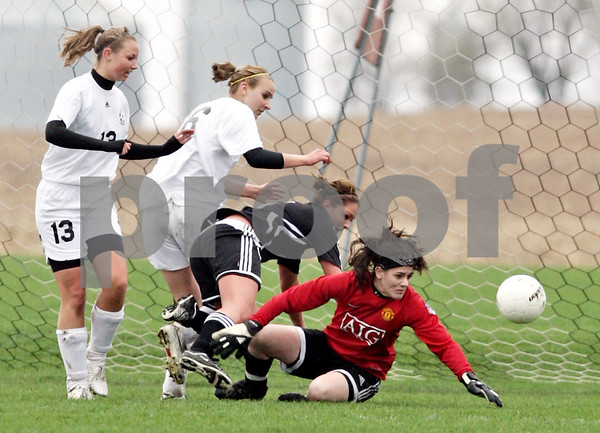 Beck Diefenbach  -  bdiefenbach@daily-chronicle.com<br /> <br /> (From left) Kaneland's Natalie Swieca (13), Savannah Webb (16), and Indian Creek's Carson Day (5) watch as Kaneland goal keeper Jordan Ginther extends to block a shot during the first half of the game at Kaneland High School in Maple Park, Ill., on Wednesday April 7, 2010. Kaneland defeated Indian Creek 7 to 0.