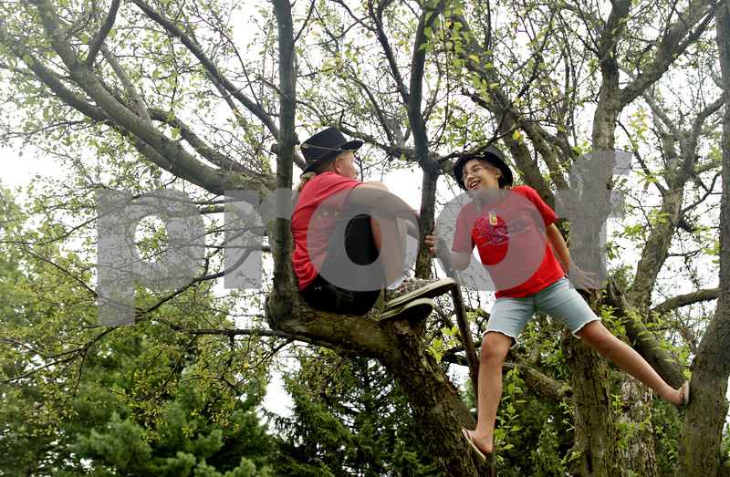 Beck Diefenbach  -  bdiefenbach@daily-chronicle.com<br /> <br /> Wearing Abe Lincoln tophats, Elena Johanson (left), 11, of Rockford, and Meaghan Heimbach, 11, of Rockford, climb a tree before the start of Kishwaukee Fest Kruise Night in DeKalb, Ill., on Friday July 30, 2010.