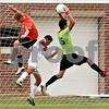 Beck Diefenbach – bdiefenbach@daily-chronicle.com<br /> <br /> Genoa-Kingston goal keeper Ivan Ortega (far right) snaps the ball above Byron's Adam Varilek (5, left) and G-K's Ulyses Parra (15, center) during the first half of the game at G-K High School in Genoa, Ill., on Thursday Sept. 23, 2010. G-K defeated Byron 2 to 1 in overtime.