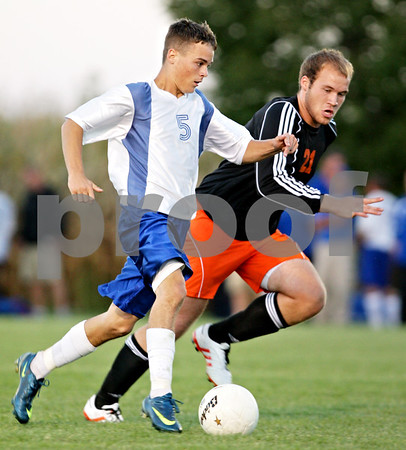 Beck Diefenbach – bdiefenbach@daily-chronicle.com<br /> <br /> Hinckley-Big Rock's Bernie Conley (5, left) controls the ball ahead of DeKalb's Steven Murphy (21) during the first half of the game at H-BR High school in Hinckley, Ill., on Monday Sept. 13, 2010. DeKalb defeated H-BR 1 to 0.