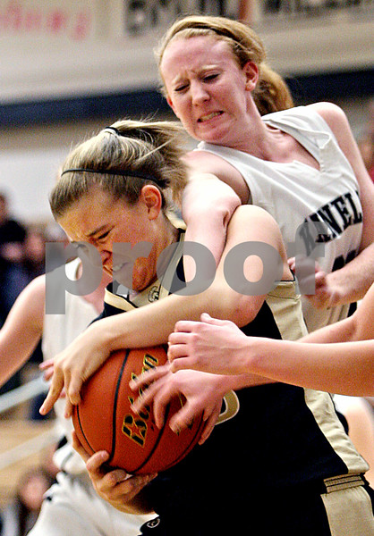 Rob Winner – rwinner@daily-chronicle.com<br /> Sycamore's Kelcee Miller secures a loose ball and the arm of Kaneland's Mallory Carlson during the first quarter of their game in Maple Park, Ill. on Saturday February 6, 2010. Sycamore defeated Kaneland, 43-39.