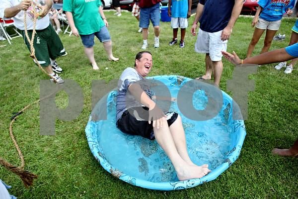 Rob Winner – rwinner@daily-chronicle.com<br /> <br /> Opportunity House client Joe Becker falls into a pool after a tug of war contest at the Opportunity House in Sycamore, Ill. on Tuesday July 27, 2010. Members of the Kishwaukee Family YMCA visited the Opportunity House for a day of competition.