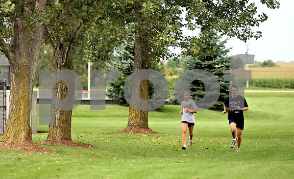 Rob Winner – rwinner@daily-chronicle.com<br /> <br /> Desarae Diedrich (left) and coach coach Mike Wolf run during cross country practice in DeKalb, Ill. on Wednesday August 18, 2010.