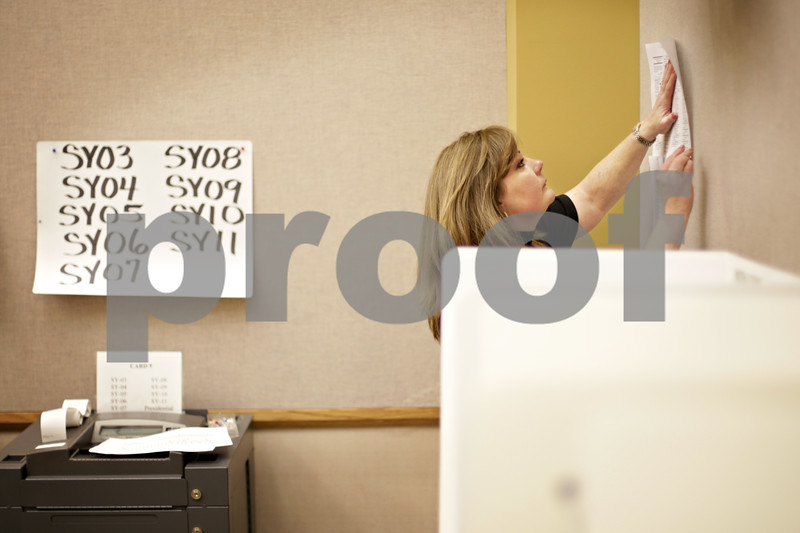 Beck Diefenbach  -  bdiefenbach@daily-chronicle.com<br /> <br /> Deputy clerk Julie Nollkamper hangs a sample ballot next to voting booths on the first day of early voting at the DeKalb County Legislative Building in Sycamore, Ill., on Monday Jan. 11, 2009.