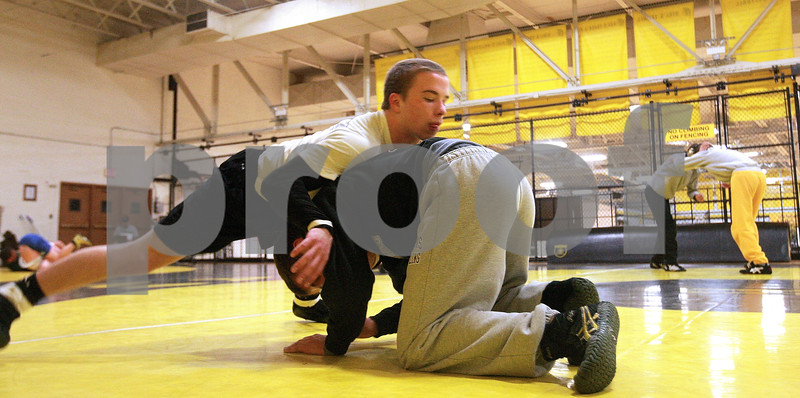 Kyle Bursaw – kbursaw@daily-chronicle.com<br /> <br /> Sycamore's Austin Coulton grabs hold of teammate Tom Ernster while doing drills during practice on Tuesday, Dec. 28, 2010 at Sycamore high school.