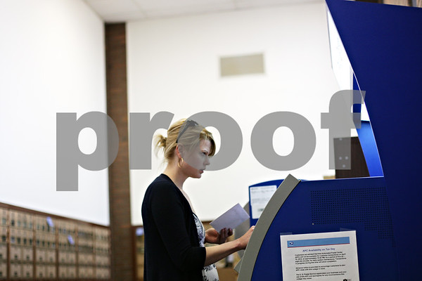 Beck Diefenbach  -  bdiefenbach@daily-chronicle.com<br /> <br /> Mindy Scheuer, a Northern Illinois University student from Chicago, uses the Automated Postal Center to mail her tax forms at the DeKalb Post Office in DeKalb, Ill., on Wednesday April 14, 2010.