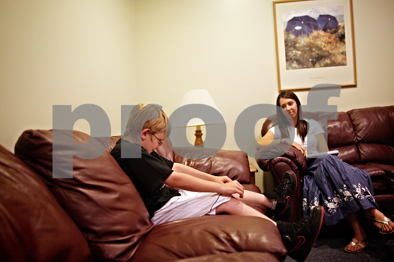 Beck Diefenbach  -  bdiefenbach@daily-chronicle.com<br /> <br /> Intern therapist Krys Sarkady, right, listens to Andrew Parker, 10, talk during a family counseling session at the Youth Services Bureau in DeKalb, Ill., on Monday June 28, 2010. Laid off from the YSB as a paid therapist, Sarkady returned to work as an unpaid intern therapist.