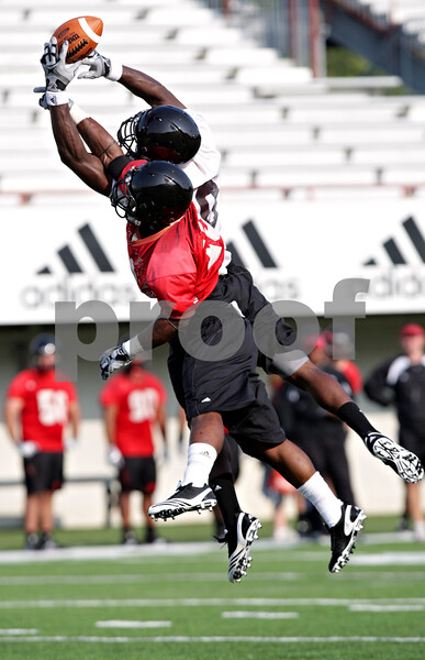 Beck Diefenbach - bdiefenbach@daily-chronicle.com<br /> <br /> Northern Illinois' wide receiver Landon Cox (80, top) attempts to catch a pass above cornerback Kiaree Daniels (23) during the first practice at Huskie Stadium in DeKalb, Ill., on Thursday Aug. 5, 2010.