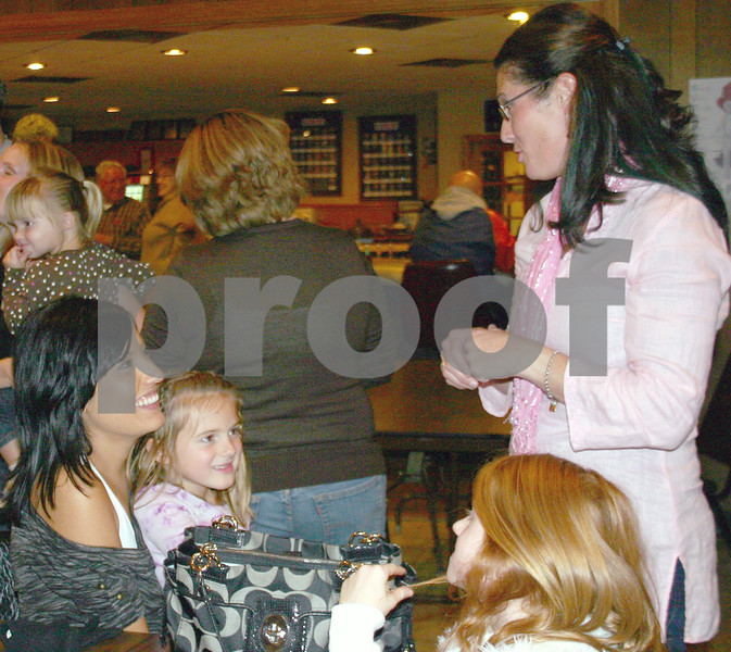 Erica Scalf (right) and her daughter, Allisan Scalf, 8, catch up with former First Friends Daycare Center employee Danielle Miller (left) and Ella Muermann, 6,  Friday at a fundraiser for employees who lost their jobs after the day care center closed last summer.<br /> <br /> By Nicole Weskerna nweskerna@daily-chronicle.com