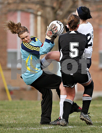 Beck Diefenbach  -  bdiefenbach@daily-chronicle.com<br /> <br /> Indian Creek goalie Kaylee Berg (left) is knocked over by Hiawatha's Valentina Andrianopoulos (20, right) during the first half of the game at Hiawatha High School in Kirkland, Ill., on Thursday March 25, 2010.