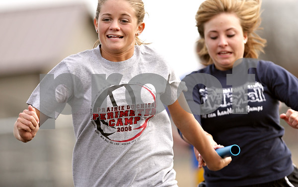 Beck Diefenbach  -  bdiefenbach@daily-chronicle.com<br /> <br /> Genoa-Kingston's Molly Meier (left) receives the baton during track practice at Genoa-Kingston High School in Genoa, Ill., on Tuesday March 16, 2010.