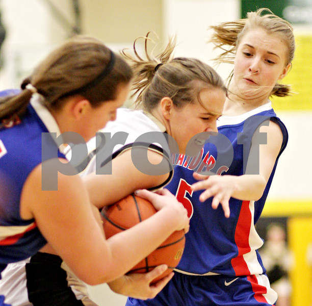 Beck Diefenbach  -  bdiefenbach@daily-chronicle.com<br /> <br /> Sycamore's Ashley Berlinski (20, center) struggles to hold onto the ball amid Glenbard South's Colleen O'Brien (34, left) and Elisa Anderson (5, right) during the first quarter of the game at Sycamore High School in Sycamore, Ill., on Tuesday Feb. 2, 2010.