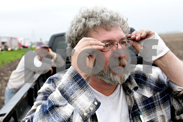 Beck Diefenbach  -  bdiefenbach@daily-chronicle.com<br /> <br /> Chauncey Watson uses Daily Chronicle photojournalist Beck Diefenbach's glasses to view his home as it destroyed by fire in rural DeKalb, Ill., on Friday April 30, 2010. Watson's glasses were lose when he was blown several feet after his home exploded.