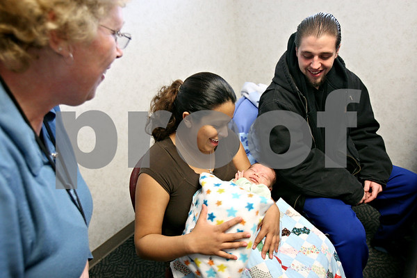 Rob Winner – rwinner@daily-chronicle.com<br /> While visiting the DeKalb County Health Department in DeKalb, Ill. on Wednesday January 6, 2009, Kay Chase, R.N. (left) gives Ana Calvillo and Jonathan Efstathiou, of Sycamore, a layette and a quilt for their three week old son, Jonathan Jr. The layette and quilt were put together and donated by the First Congregational United Church of Christ in DeKalb.