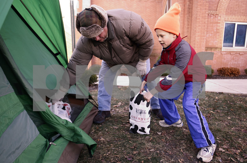 Kyle Bursaw – kbursaw@daily-chronicle.com<br /> <br /> Pack 140 assistant Cub master Jim Reuscher and Andrew Geiger, right, load up a tent with non-perishable items during their 'Camping for Cans' drive where the pack collects donations at St. Mary's Church in Sycamore. <br /> <br /> Saturday, Nov. 27, 2010.