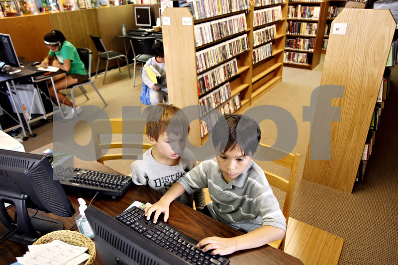 Rob Winner – rwinner@daily-chronicle.com<br /> <br /> Kyler Hooker (left), 5, watches as his brother Keagan Vaje, 9, plays an online game on a computer at the Cortland Public Library in Cortland, Ill. on Friday October 8, 2010.