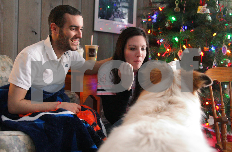 Kyle Bursaw – kbursaw@daily-chronicle.com<br /> <br /> Kevin Ballantine and his girlfriend Holly Swaim smile and look at the Ballantine's dog Gracie as she approaches smelling Swaim's french fries while the couple watches the Chicago Bears game on Dec. 12, 2010.