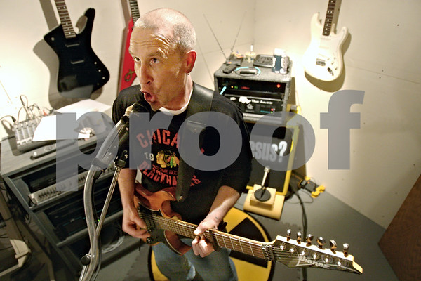 Rob Winner – rwinner@daily-chronicle.com<br /> <br /> Dave Young, of the DeKalb Christian Church, rocks out in the basement of his Cortland home during band practice on Wednesday March 17, 2010.