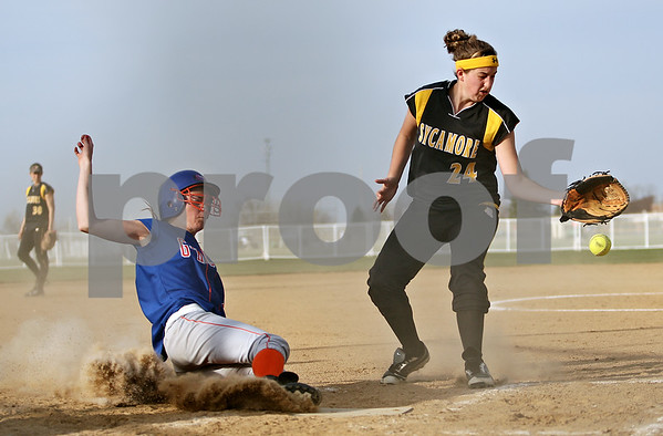 Beck Diefenbach  -  bdiefenbach@daily-chronicle.com<br /> <br /> Genoa-Kingston's Kelsie Campbell (2, left) slides safe into home as Sycamore's Nekoda Garbes (24) misses the ball during the top of the fifth inning at Sycamore High School in Sycamore, Ill., on Thursday April 1, 2010. G-K defeated Sycamore 9 to 2.