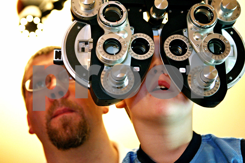 Rob Winner – rwinner@daily-chronicle.com<br /> <br /> Five-year-old Isaac Thibeault, of Sycamore, has his eyes examined while sitting on the lap of his father, Jason Thibeault, at Spex Express in Sycamore, Ill. on Wednesday August 18, 2010.