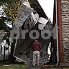 Kyle Bursaw - kbursaw@daily-chronicle.com<br /> <br /> Gary Tadd of Pinkston Tadd Roofing Services assesses the damages to 916 Greenbrier Road, where wind gusts blew the roof off of the building. Tadd's company has been contracted to start on putting on a new roof starting tomorrow. 10.27.10