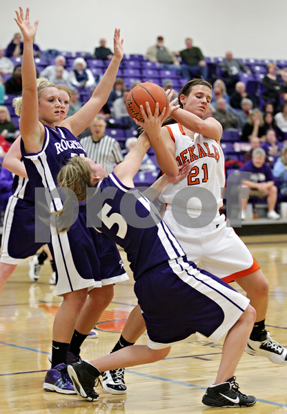 Beck Diefenbach  -  bdiefenbach@daily-chronicle.com<br /> <br /> DeKalb's Kelli Gerace (21, right) tries to keep the the ball away from Rochelle's Olivia Caron (5, bottom) during the second quarter of the IHSA Class 3A Regional game at Rochelle Township High School in Rochelle, Ill., on Wednesday Feb. 17, 2010