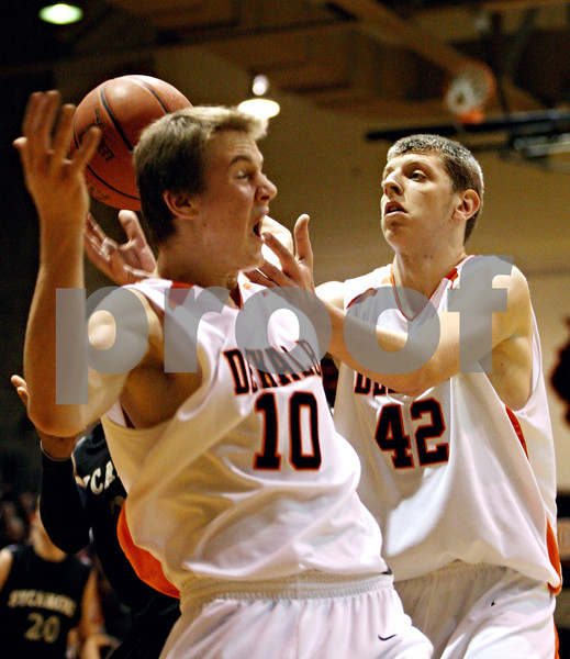 Rob Winner – rwinner@daily-chronicle.com<br /> DeKalb's Chris Calbow (10) and Jordan Threloff (42) look to secure a rebound under the Sycamore basket during the fourth quarter. DeKalb went on to defeat Sycamore, 53-43, on Saturday February 20, 2010 in DeKalb, Ill.