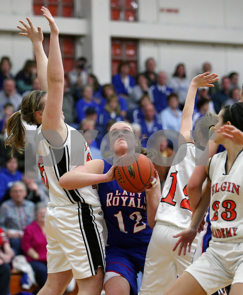 Rob Winner – rwinner@daily-chronicle.com<br /> Hinckley-Big Rock's Katie Hollis battles through a trio of Elgin Academy defenders to put up a shot for two in the second half of Thursday night's sectional game. Hinckley-Big Rock defeated Elgin Academy, 62-35.