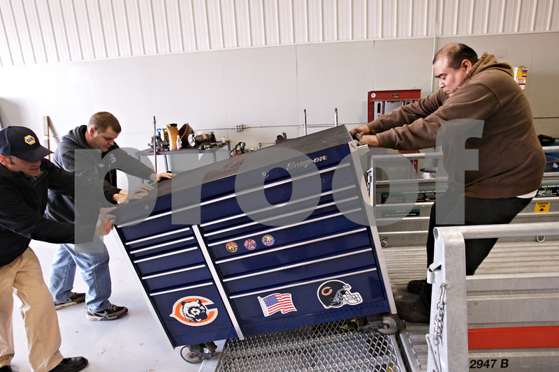 Beck Diefenbach  -  bdiefenbach@daily-chronicle.com<br /> <br /> (From left) Shop manager Sam Bond, John Daniels and mechanic Faron Begay unload Begay's tools from a trailer as they move into Bockman's Auto Care's new location at 2158 Oakland Dr. in Sycamore on Monday March 29, 2010.
