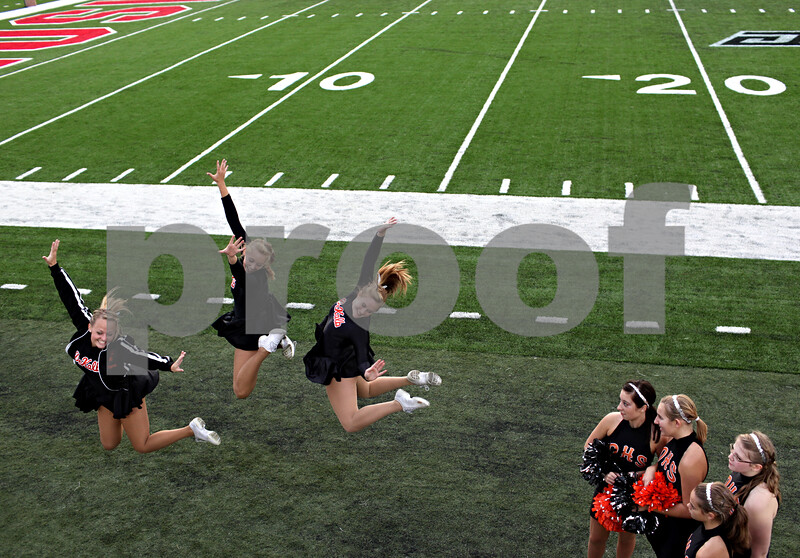 Beck Diefenbach – bdiefenbach@daily-chronicle.com<br /> <br /> DeKalb poms dancers (from left) Emily Phelps, Kelsey Olsen and Hannah Latimar leap into the air before the start of the Castle Challenge football game between DeKalb and Sycamore High Schools at Huskie Stadium on the campus of Northern Illinois University in DeKalb, Ill., on Friday Sept. 10 2010.