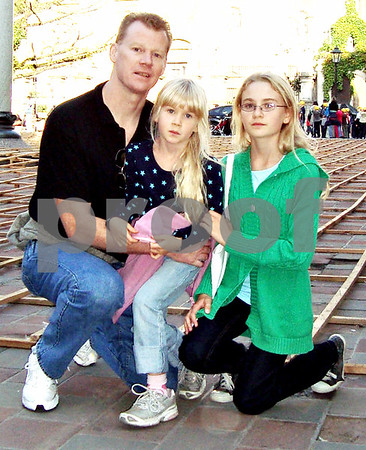 In September of 2009 Sean McKnight (left to right) poses for a photograph with his children Julia, now 7, and Kelly, now 14, in Krakow, Poland.