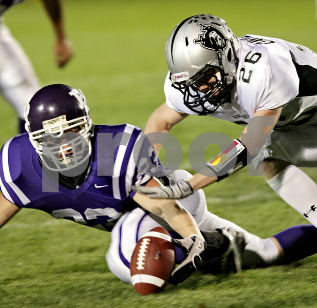 Beck Diefenbach – bdiefenbach@daily-chronicle.com<br /> <br /> Kaneland defensive back Kyle Davidson (26, right) and Rochelle's Will Metzger (23) chase a Rochelle fumble during the first quarter of the game at Rochelle High School in Rochelle, Ill., on Friday sept. 24, 2010.