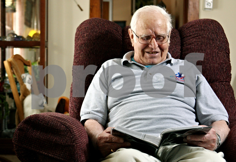 Rob Winner – rwinner@daily-chronicle.com<br /> <br /> On Saturday March 20, 2010, Leo McDermott, who served in the Air Force during World War II, sits in his favorite chair at his home in DeKalb, Ill. while looking through a photo album from a recent trip to Washington D.C. which was paid for by Honor Flight Chicago.