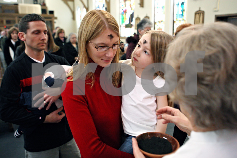 Rob Winner – rwinner@daily-chronicle.com<br /> The Gullo family which includes Kendall (from left), Talon, 3 months, Holly and Savannah, 3, of Wausau, Wis., receive ash crosses on their foreheads from Teri Lorek during Lent service at St. Mary Parish in DeKalb, Ill. on Wednesday February 17, 2010.