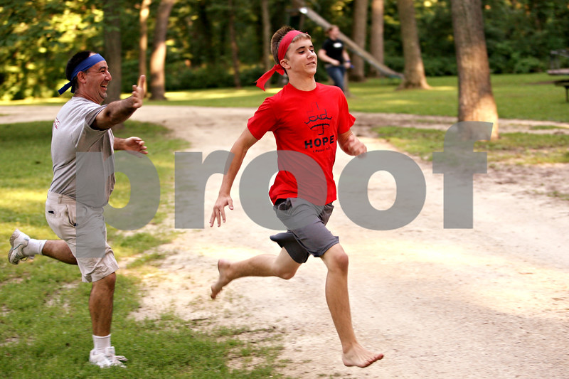 Beck Diefenbach  -  bdiefenbach@daily-chronicle.com<br /> <br /> Greg Oidtman, left, of Kenilworth, chases down Nathan Wade, of Aurora, during a capture the flag tournament at Chief Shabbona Forest Preserve for youth members of the Village Bible Church on Wednesday June 30, 2010.