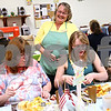 Beck Diefenbach  -  bdiefenbach@daily-chronicle.com<br /> <br /> Volunteer Cindy Lumpkin (top) shares a laugh with Richelle Nowles (left), of DeKalb, and Samantha Wood, of DeKalb, after serving them ice cream during the biweekly VAC community dinner at the Senior Services Center in DeKalb, Ill., on Wednesday March 31, 2010. Lumpkin works for Heritage Woods which sponsored Wednesday's dinner