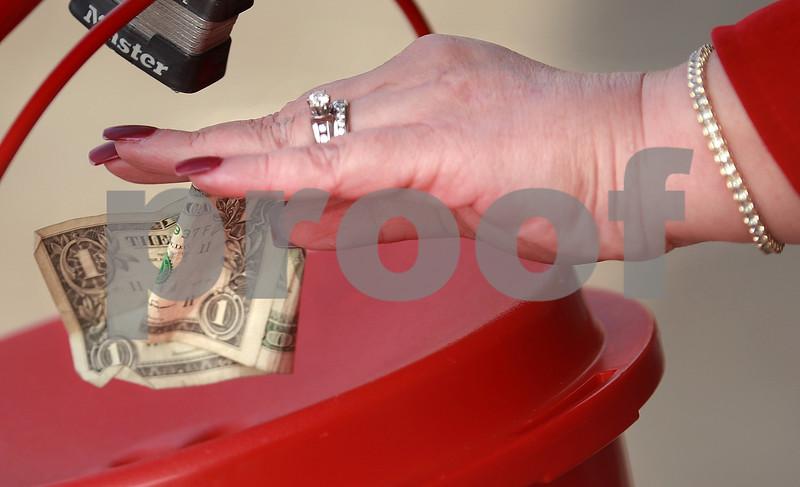 Kyle Bursaw – kbursaw@daily-chronicle.com<br /> <br /> A Jewel-Osco shopper drops some money into the Salvation Army bucket on Friday, Nov. 19, 2010, in DeKalb, Ill.