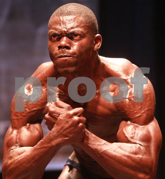 Kyle Bursaw – kbursaw@daily-chronicle.com<br /> <br /> Bodybuilder Samuel Okunola flexes to show off his muscles as they are judged at the Egyptian in DeKalb, Ill. on Saturday, Nov. 20, 2010.