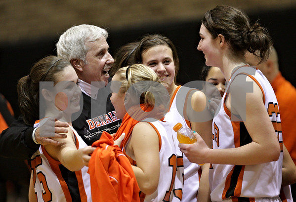 Beck Diefenbach  -  bdiefenbach@daily-chronicle.com<br /> <br /> DeKalb's Dave Pettengell is embraced by the girls basketball team following their loss to Geneva at DeKalb High School, in DeKalb, Ill., on Friday Jan. 5, 2010.