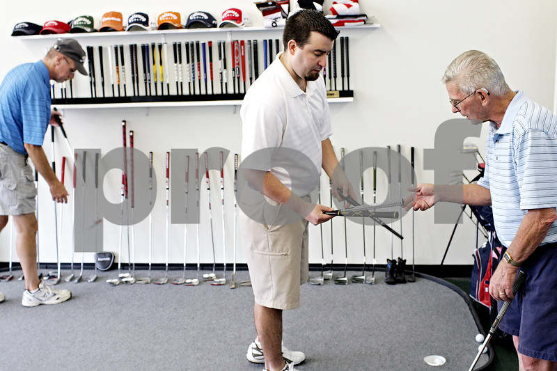 Beck Diefenbach  -  bdiefenbach@daily-chronicle.com<br /> <br /> Store vice president Dan Peck (center) shows off a selection of golf club grips to Ron Burright (right), of DeKalb, in Diamond Tour Golf shop in downtown DeKalb on Thursday June 10, 2010. Originally an online and phone orders-only company, Diamond Tour Golf recently opened a store front.