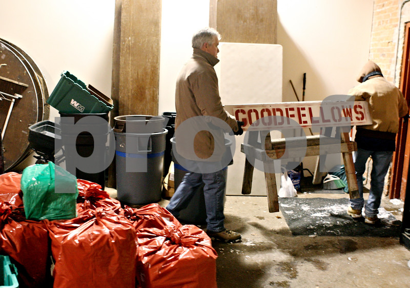 Rob Winner – rwinner@daily-chronicle.com<br /> <br /> Tom Doty (left) and Gerry Keating, both of Sycamore, carry a Goodfellows sign outside Blumen Gardens in Sycamore on Tuesday night. Volunteers gathered at the site to wrap gifts that will be distributed on Friday morning to needy families.